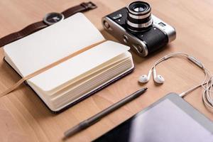 caderno em branco aberto, câmera antiga, tablet, fones de ouvido, relógio e caneta foto