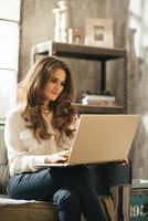jovem mulher usando laptop enquanto está sentado no apartamento loft foto