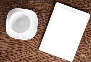 computador tablet e xícara de café vazia no fundo de madeira velho foto