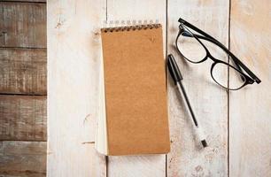 bloco de notas, óculos e caneta de tinta foto