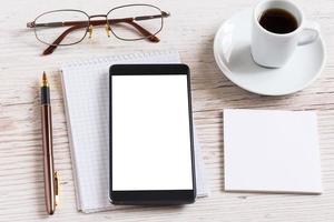 notebook com óculos, lápis, telefone inteligente e xícara de café
