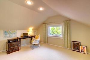 escritório no sótão bege com móveis simples. foto