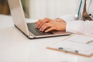 médico mulher trabalhando no laptop. fechar-se foto