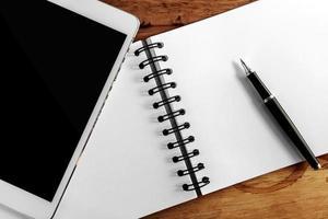 tela de computador, livro e caneta na mesa de madeira foto