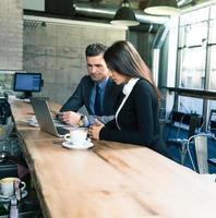 empresário e empresária usando laptop no café