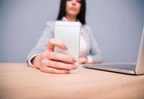 empresária, sentado à mesa e segurando o smartphone foto