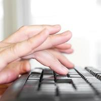 mãos no teclado do computador foto