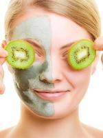 mulher com máscara facial de argila cobrindo os olhos com kiwi
