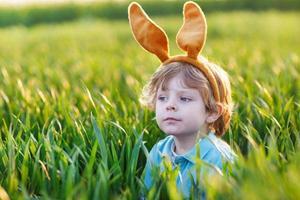criança pequena bonita com orelhas de coelho de Páscoa brincando na grama