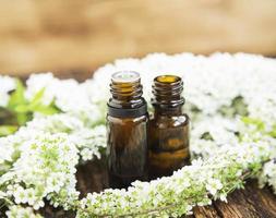 garrafas de essência de flores brancas foto