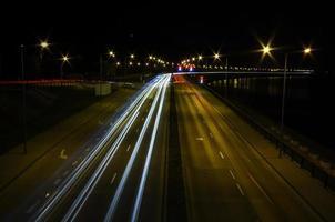 trilhas leves de carros, de trânsito em movimento na rua foto