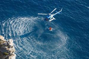 helicóptero de bombeiros coletar água sobre o mar foto