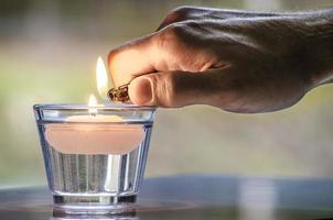 mão com isqueiro acender uma vela foto