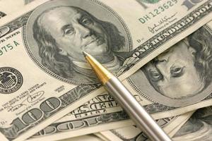 caneta e dólares americanos