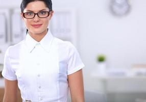 mulher de negócios atraente com os braços cruzados em pé no escritório