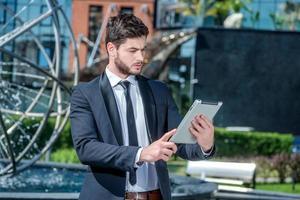 no tablet. empresário confiante e bem sucedido, segurando um foto