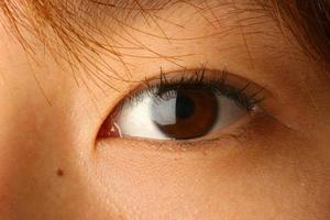 close-up de um olho asiático marrom com luz refletida nele