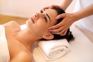 mulher jovem e bonita recebendo um tratamento de rosto no salão de beleza. foto