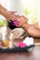 jovem mulher recebendo massagem na cabeça foto