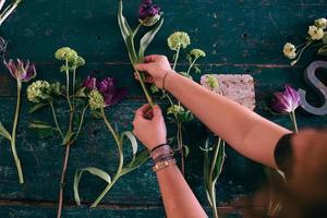 espaço de trabalho do florista: mulher fazendo decorações florais foto