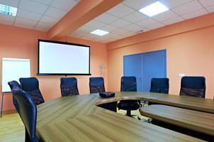 sala de conferências com cadeiras vazias e uma tela de projetor foto