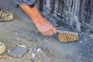 trabalhador da construção civil com vassoura varrendo concreto 3 foto