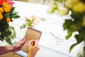 florista com bloco de notas foto