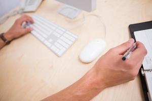 mãos usando o teclado do computador e o diário na mesa foto