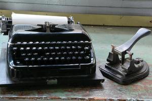 máquina de escrever e perfurador em uma mesa foto