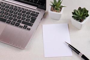 computador portátil, suculentas, papel em branco na mesa de escritório. foto