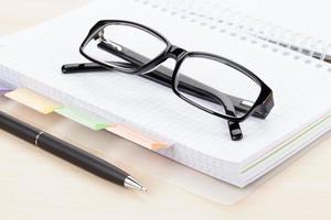 mesa de escritório com óculos sobre o bloco de notas foto