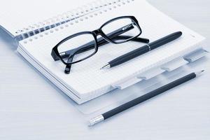mesa de escritório com óculos, bloco de notas em branco e lápis foto