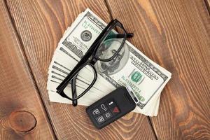 chave remota de dinheiro, óculos e carro foto