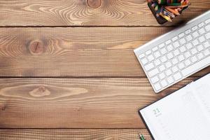 mesa de escritório com teclado e suprimentos foto