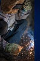 trabalhador de soldador de arco na máscara protetora, construção de metal de solda