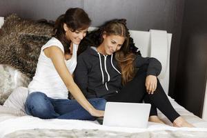 dois amigos usando laptop foto