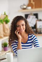 mulher jovem sorridente com uma xícara de café e laptop no foto