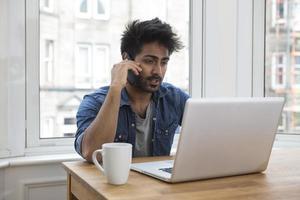 homem asiático em casa trabalhando no laptop. foto