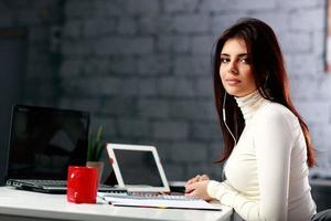 empresária, sentado à mesa no seu local de trabalho
