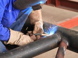soldador está soldando a estrutura do tubo com toda a segurança foto