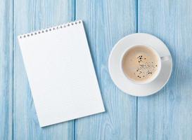 xícara de café e bloco de notas em branco foto