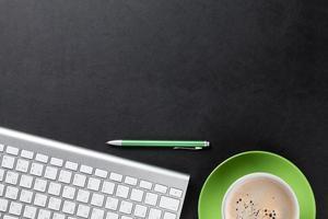 mesa com computador, caneta e café