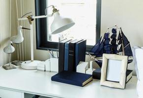 mesa de trabalho com lâmpada, lápis, livros em uma casa