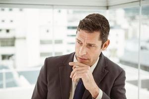 empresário pensativo olhando para longe no escritório