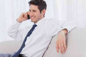 empresário sorrindo e chamando no sofá foto
