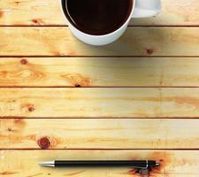 xícara de café e caneta em uma mesa de madeira foto