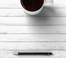 xícara de café com caneta e lugar para você texto foto