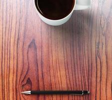 xícara de café, caneta e local para o seu texto foto