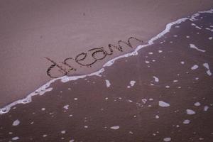 sonhadora palavra escrita na areia foto