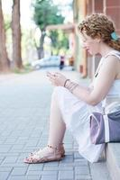 menina loira encaracolada no telefone foto